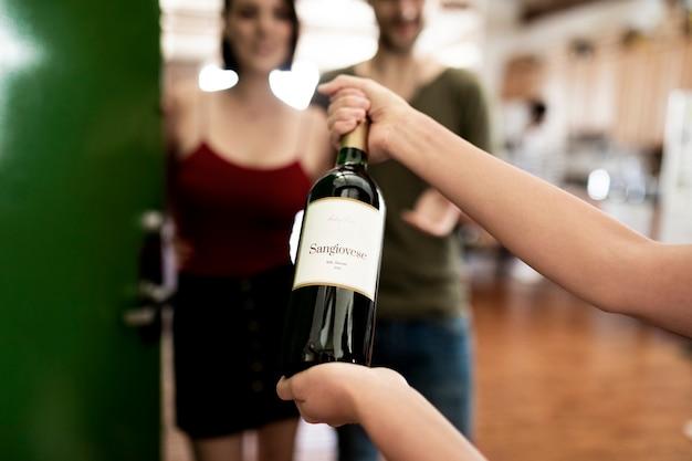赤ワインのボトルを提示する女性