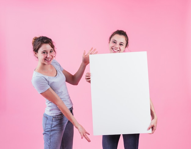 Woman presenting blank placard hold by her friend against pink background