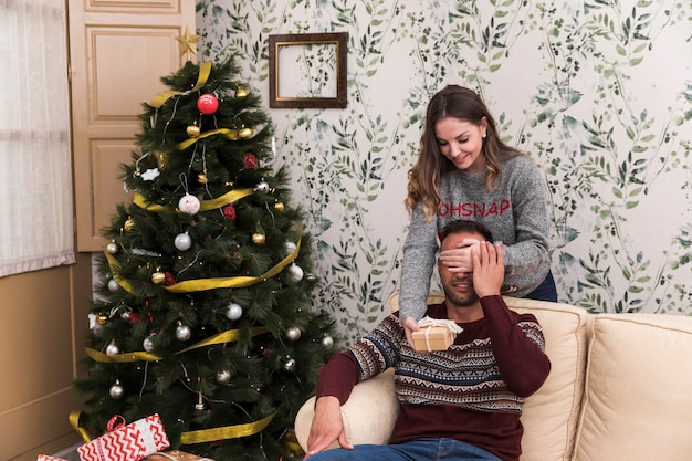 Woman presenting gift box and closing eyes to man on settee near christmas tree