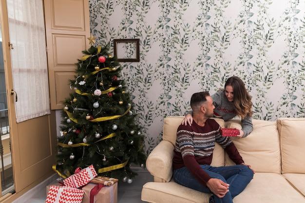 Woman presenting gift box to man on settee near christmas tree