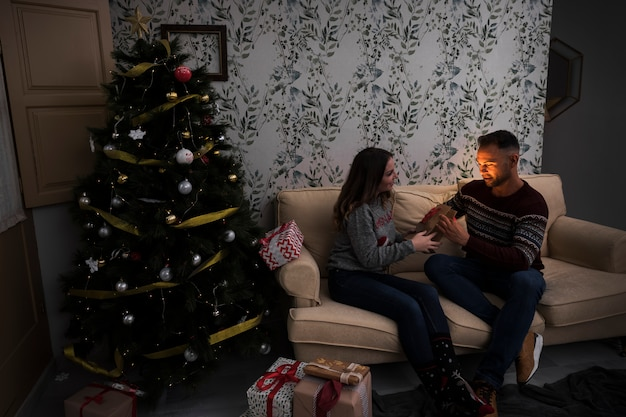 Woman presenting gift packet to man on settee near christmas tree in room