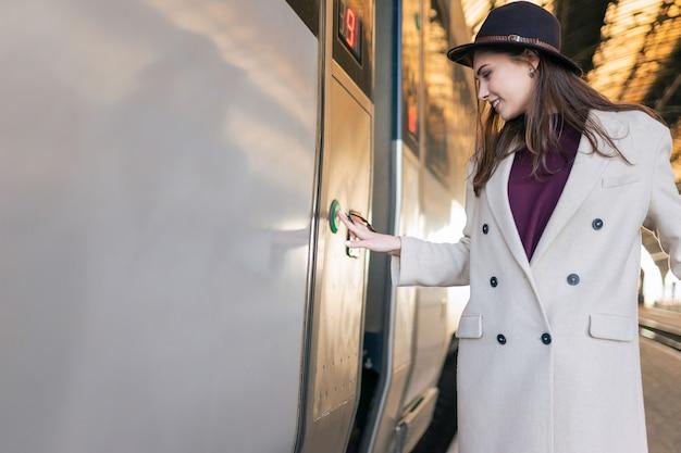 Женщина нажимает кнопку на двери поезда