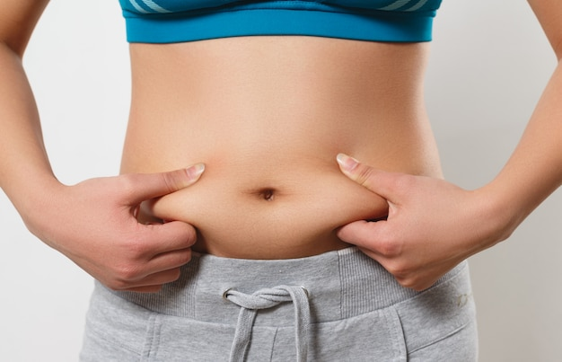 The woman presses her fingers to the folds of fat on the sides of her stomach
