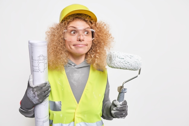 Woman presses lips focused into distance wears protective helmet uniform and safety glasses being professional decorator holds roller blueprint poses indoor. home repair service