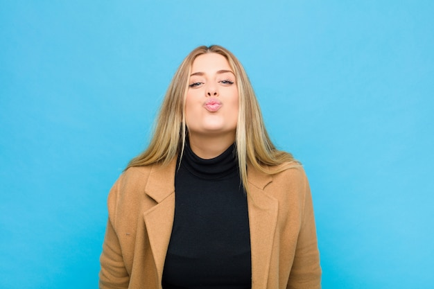 Woman pressing lips together with a cute, fun, happy, lovely expression, sending a kiss