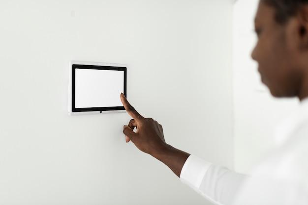 Женщина нажимает на монитор панели умной домашней автоматизации