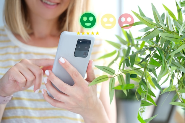Woman pressing smiley face on mobile phone closeup customer evaluation concept