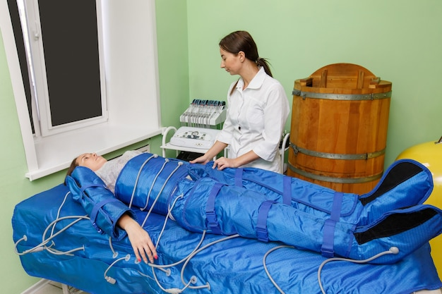 Woman in pressotherapy suit having pressure therapy for weight loss