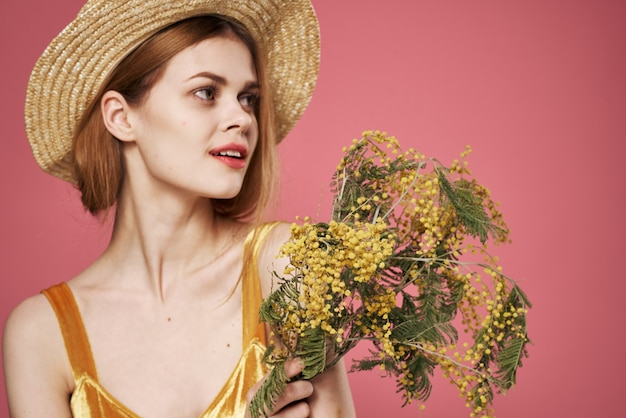 女性きれいな女性の花束ミモザホリデーギフトピンクの背景。高品質の写真