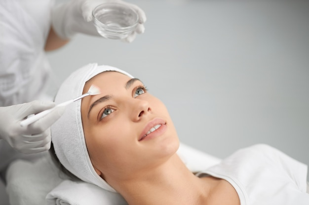 Woman on procedure for face in beautician