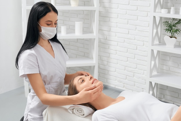 Woman on procedure massage for face in beautician