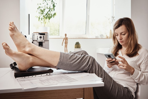 Женщина откладывает удаленную работу. фрилансер использует смартфон в домашнем офисе