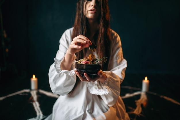Женщина производит ритуал черной магии, оккультизма.