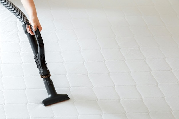 Woman do professional cleaning mattress by vacuum cleaner from dust bacteria dirty. vacuum cleaner machine in female hand do disinfection surfaces, cleanliness in hotel apartment. copy space.