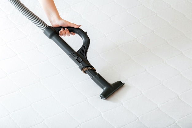 Woman do professional cleaning mattress by vacuum cleaner from dust bacteria dirty. vacuum cleaner machine in female hand do disinfection surfaces, cleanliness in hotel apartment.
