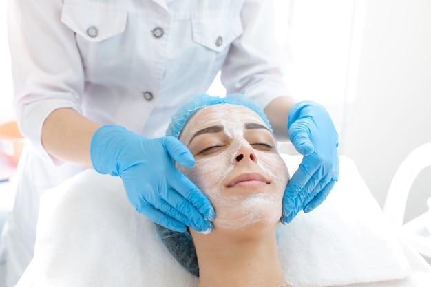 女性専門医の美容師がスキンケアのために患者の顔にマスクを適用します