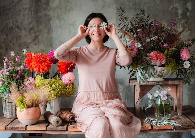 ユーモアの女性専門の花屋は、組成野生の花を持つ木製のテーブルに座っている花目でポーズします。