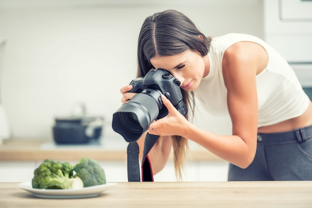 브로콜리와 함께 여자 전문 사진 접시입니다. 주방 스튜디오에서 일하는 음식 사진작가.