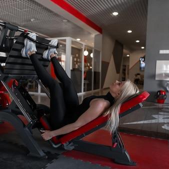 검은 옷을 입은 여성 전문 트레이너가 다리 운동을 올바르게하는 방법을 보여줍니다.