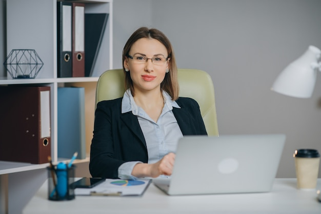 Woman professional using laptop sit at office desk, happy female customer make confirming online website.