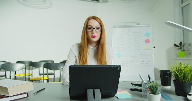 テーブルに座って、クラスでオンライン講義をしている女性教授。