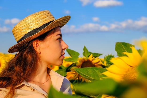 Портрет профиля женщины в соломенной шляпе в зацветая поле подсолнечника на восходе солнца.