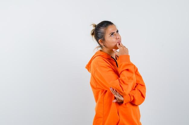 Donna che appoggia il mento sulle dita in felpa con cappuccio arancione e sembra pensierosa