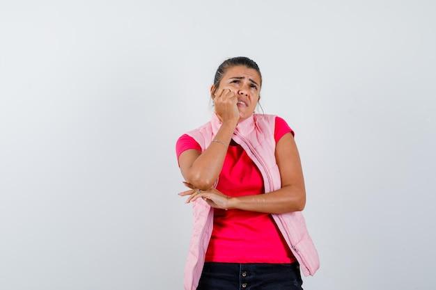 Donna che appoggia il mento sulla mano in maglietta, gilet e sembra triste