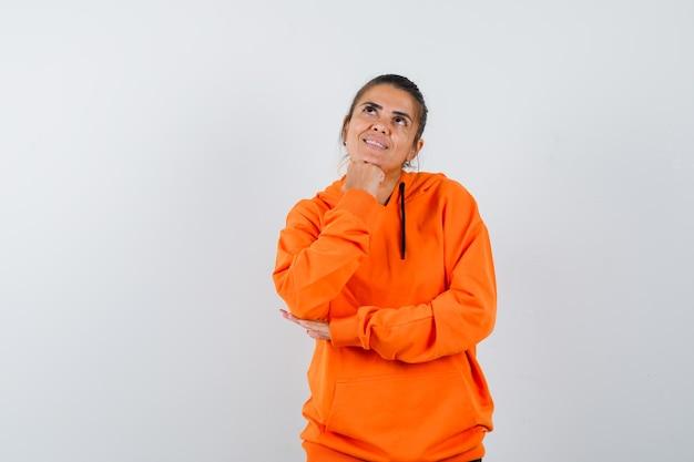 オレンジ色のパーカーで拳で顎を支え、希望に満ちた女性