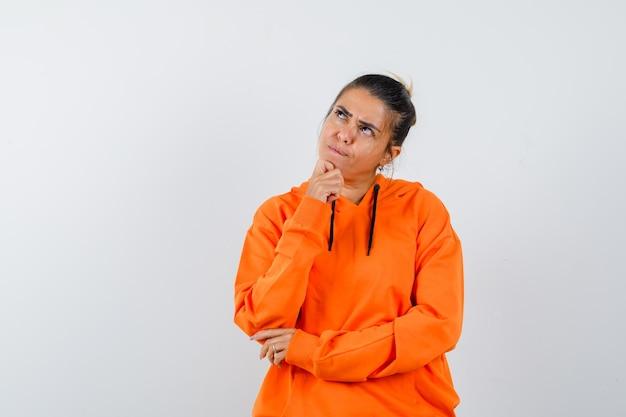 Женщина, подпирающая подбородок рукой в оранжевой толстовке с капюшоном, нерешительно выглядит