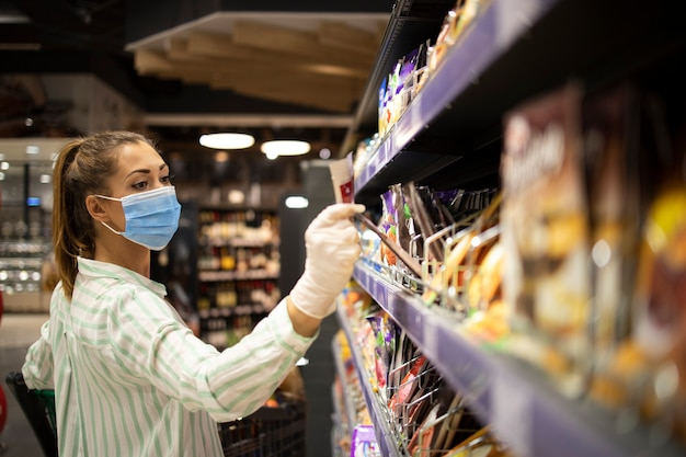Woman protecting herself against corona virus while shopping in supermarket