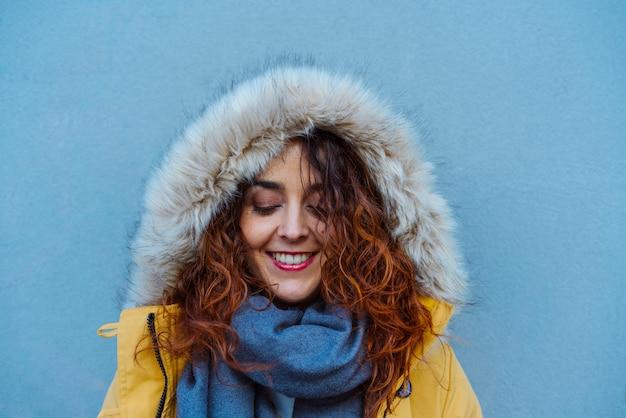 Женщина защищает себя с капюшоном от зимних дождей