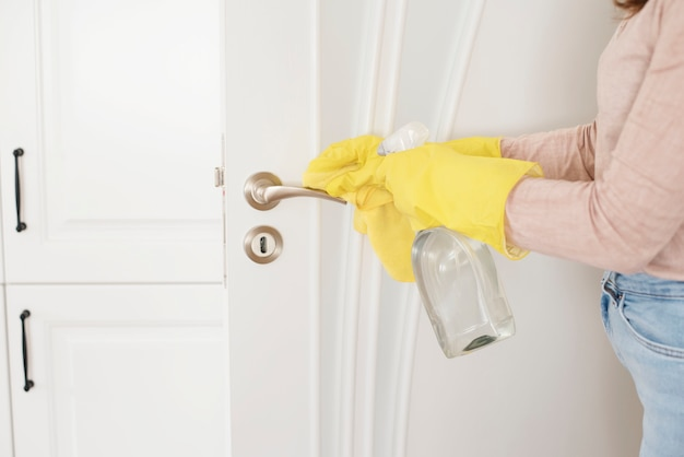 Woman in protective gloves disinfecting door handle while cleaning at home