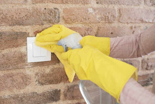 Woman in protective gloves disinfecting wall switches while cleaning at home