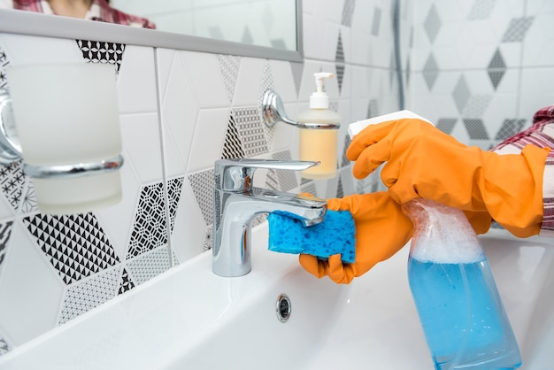 Woman in protective gloves holding a spray and a rag doing chores in bathroom, cleaning of water tap.