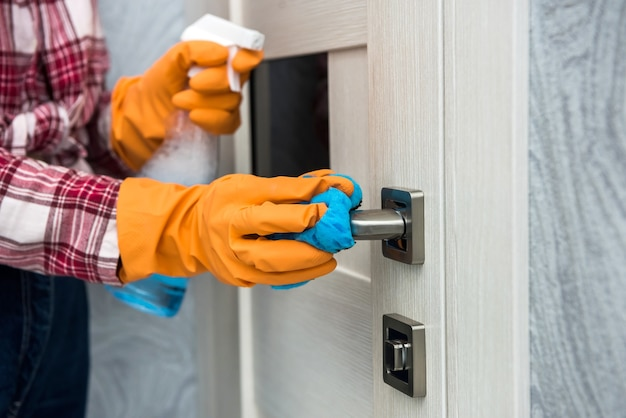 Woman in protective gloves holding a spray and a rag while cleaning her house.