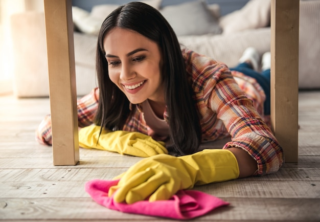 Woman in protective gloves is smiling, cleaning using a detergent.