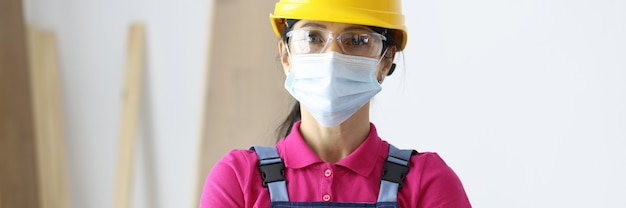 Woman in protective helmet wearing medical mask on face standing at construction site.repair services during covid-19 pandemic concept