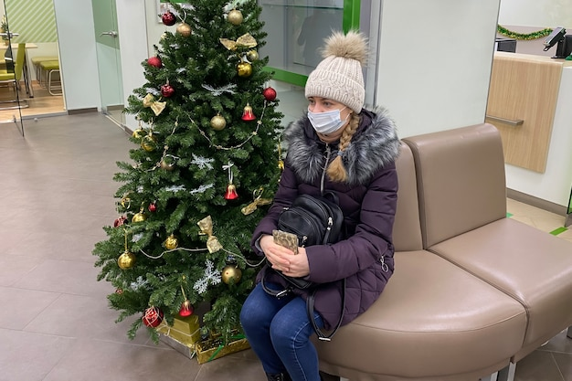 Woman in a protective mask is alone in an empty bank waiting for a specialist's consultation