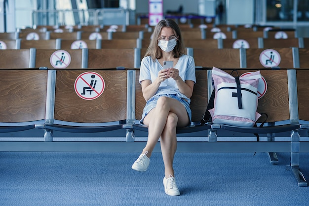 Woman in protective mask waiting for the plane at the airport beautiful girl uses mobile phone at