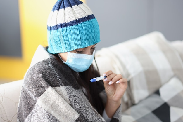 Woman in protective mask and warm hat sitting under covers and looking at thermometer