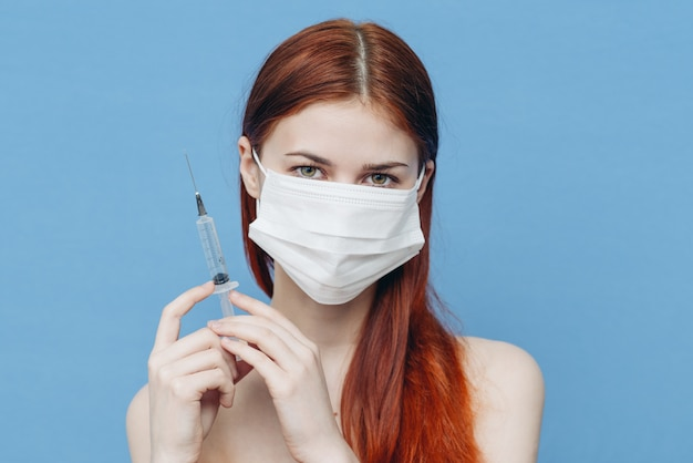 Woman in a protective mask with a syringe, blue wall