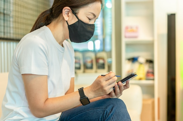 Woman in protective mask working on smart phone using digital pen.