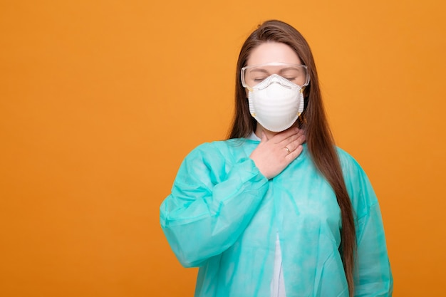 Woman in protective medical equipment with medical mask on face on  yellow  symptom of illness coronavirus pandemic sore throat cough