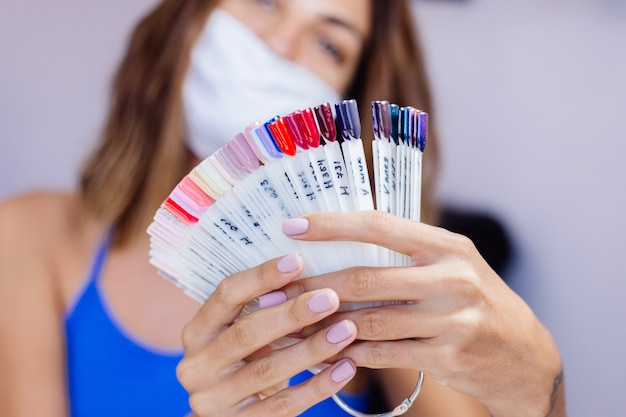 Woman in protective medical mask in beauty salon hold palette and select a color manicure procedure nail care grand opening quarantine is over small businessess are open again