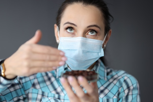 Woman in protective medical mask tries to smell coffee. loss of smell in coronavirus concept