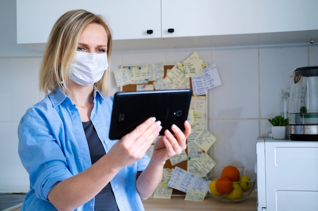 Woman in protective medical mask using digital tablet for video call talking friends and parents, girl sitting at home kitchen fun greeting online by computer webcam making videocall