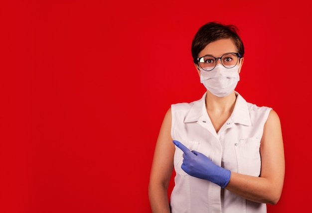 A woman in a protective suit against the covid-19 virus indicates the direction.