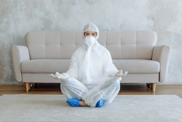 A woman in a protective suit for disinfecting household items and furniture is meditating in a room. home disinfection