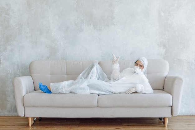 A woman in a protective suit for disinfection of household items and furniture shows a sign while lying on a sofa.